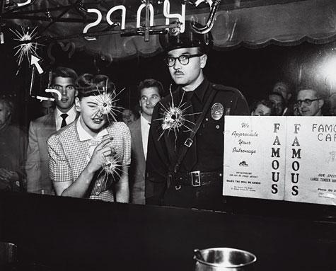"""Fotografía anónima © University of Southern California / Regional History Center Un grupo de curiosos acompaña a la policía en la escena de un tiroteo, 1953. De la exposición """"Los Ángeles. Historia visual de una ciudad"""", en la Fnac."""